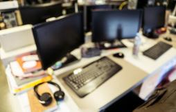Abstract blurred image of desk, computer, earphones